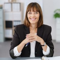 Portrait of a Cheerful Businesswoman in Black Suit Sitting at her Desk, Smiling at the Camera.